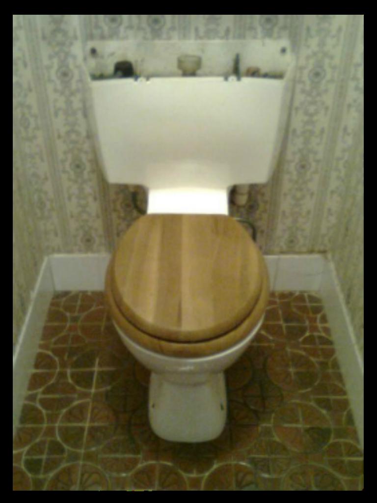 Old toilet before tapsntoilets plumber installs a new toilet